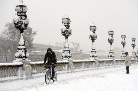 A man rides his bicycle on the snow-cove