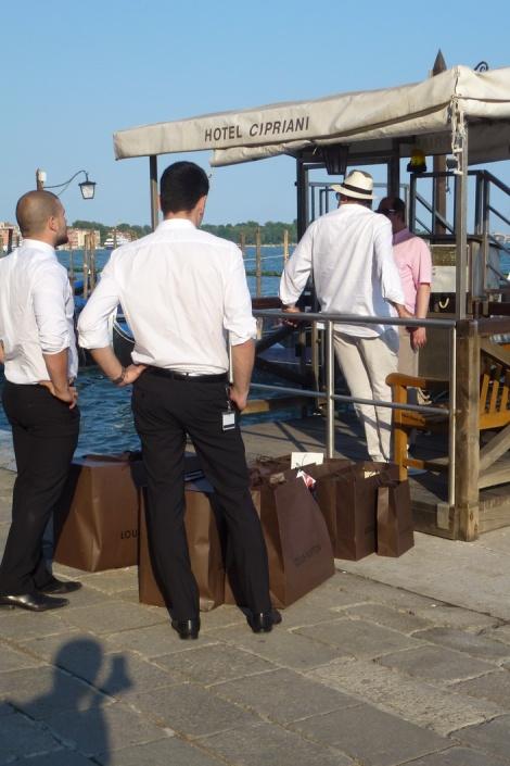 עובדי לואי ויטון משנעים סחורות ארוזות היטב למלונות הפאר הונציאנים ברציף ליד החנות