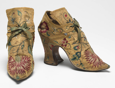 Textiles. Shoes/pumps. Silk taffeta, bound with ribbon; floss silk embroidery in French knots, long and short, satin and split stitches; tied with ribbon. Ground covered by a pattern of trailing and scrolling stems with leaves and flowers, carnation, rose, etc., so arranged that there is a carnation on each toe and a rose on each heel with a five petalled blue flower above it. The left shoe has a rose, the right a carnation at each side of the seam. Silk, length, whole, 7 in, height, back, 5.25 in, height, heel, 3 in, circa 1700-circa 1749. English.